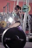 Jong sexy meisje in de gymnastiek die hurkzit op rode achtergrond doen Royalty-vrije Stock Foto
