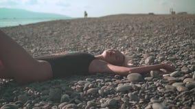 Jong sexy meisje in een zwempak die op een rotsachtige kust liggen Het blonde in een zwempak uit één stuk ligt op de stenen van h stock videobeelden