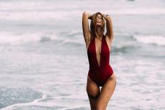 Jong sexy meisje met grote borsten in een rood zwempak die op zwart zandstrand rusten royalty-vrije stock afbeeldingen