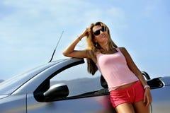 Jong sexy meisje met zonnebril die op cabrio leunen Royalty-vrije Stock Foto