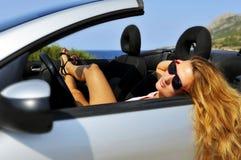 Jong sexy meisje met zonnebril die op cabrio SP liggen Royalty-vrije Stock Afbeelding