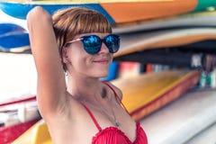 Jong sexy meisje in rood zwempak - surfer met brandingsraad het stellen op het strand van Nusa Dua, het tropische eiland van Bali Royalty-vrije Stock Afbeelding