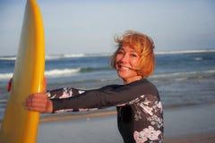 Jong sexy mooi en gelukkig surfermeisje die gele brandingsraad houden die vrolijke het genieten van de zomervakantie in tropisch  royalty-vrije stock foto's