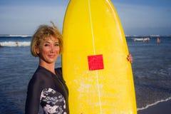 Jong sexy mooi en gelukkig surfermeisje die gele brandingsraad houden die vrolijke het genieten van de zomervakantie in tropisch  stock foto's