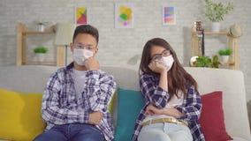 Jong sian droevig paar die in beschermende medische maskers op bank zitten stock videobeelden