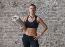 Jong skinheadwijfje met yogamat die zich dichtbij muur bevinden stock fotografie