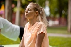 Jong slank meisje met het sluiten van ogen die yogaoefeningen op de yogamat doen op groen gras in het park op een warme dag yoga stock fotografie