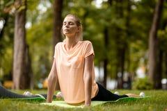Jong slank meisje met het sluiten van ogen die yogaoefeningen op de yogamat doen op groen gras in het park op een warme dag yoga royalty-vrije stock afbeeldingen