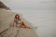 Jong slank mooi vrouwenmeisje op zonsondergangstrand, indie stijl De achtergrond van de rots stock foto