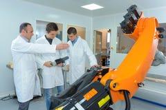 Jong slim studentenportret in robotachtig laboratorium stock fotografie