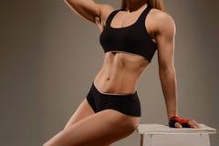 Jong sportenmeisje in bovenkant en borrels die bij stoel stellen Een mooie vorm, atletisch cijfer stock foto's