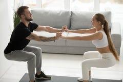 Jong sportief paar die hurkzit doen die handen samen thuis houden royalty-vrije stock foto