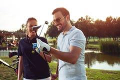 Jong sportief paar speelgolf op een golfcursus stock foto's