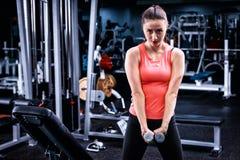 Jong sportief wijfje in sportkleding die sommige gewichten opheffen stock fotografie