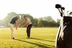 Jong sportman het praktizeren golf met zijn leraar stock foto