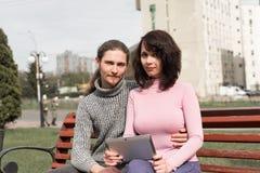 In jong studentenpaar in stad die tablet gebruiken Stock Foto's