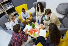 Jong team die van freelancers informatie zoeken die het bedrijfstaken raadplegen maken stock foto's