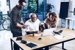 Jong team van medewerkers die grote het werkbespreking in modern coworking bureau maken Gebaarde mens die met collega's spreken Stock Fotografie
