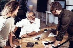 Jong team van medewerkers die grote het werkbespreking in moderne coworking studio maken Gebaarde mens die met collega's spreken Stock Foto