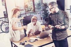 Jong team van medewerkers die grote tijdrem maken tijdens bespreking in modern bureau Het gebaarde mens lachen en meisjesholding Royalty-vrije Stock Foto