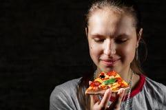 Jong tiener donkerbruin meisje die met lang haar plak van pizza op donkere zwarte muurachtergrond eten met exemplaarruimte stock afbeeldingen
