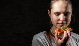 Jong tiener donkerbruin meisje die met lang haar plak van pizza op donkere zwarte muurachtergrond eten met exemplaarruimte royalty-vrije stock foto
