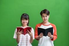 Jong tiener en meisje die en zich bij boek bij groen bevinden lezen stock fotografie