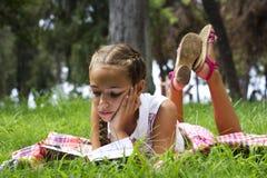 Jong tienermeisje die op groen gras liggen en boek lezen stock foto's