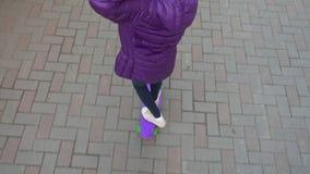 Jong tienermeisje die op skateboard op bedekte stoep in stadsstraat berijden Meisjestiener het met een skateboard rijden De jeugd stock footage