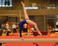 Jong turnermeisje dat routine op evenwichtsbalk uitvoert Stock Foto