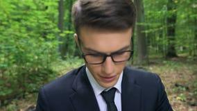 Jong van nature geïnspireerd managerhoogtepunt van ideeën die aan project in groen park werken, stock footage