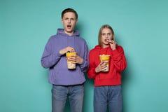 Jong verbolgen geschokt paar die in vrijetijdskleding op tegenstrijdige film letten, die emmer popcorn houden stock foto