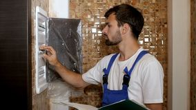 Jong volwassen de ingenieur van de elektricienbouwer het schroeven materiaal in zekeringkast stock video