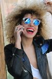 Jong volwassen krullend meisje die bij cellphone spreken Royalty-vrije Stock Afbeeldingen