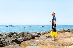 Jong vrolijk meisje in het duiken kostuum met peddels die zich op rots bevinden royalty-vrije stock afbeelding