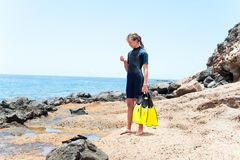 Jong vrolijk meisje in het duiken kostuum met peddels die zich op rots bevinden royalty-vrije stock afbeeldingen