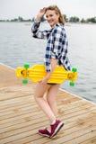 Jong vrolijk meisje in hipsteruitrusting die gele longboard in zijn hand houden en op een houten pijler lopen royalty-vrije stock foto