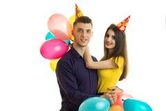 Jong vrolijk paar die zich naast elkaar met grote gekleurde ballons en hoeden in de vorm van een kegel op uw hoofd bevinden Stock Foto's
