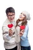 Jong vrolijk toevallig paar dat rode harten houdt Royalty-vrije Stock Fotografie