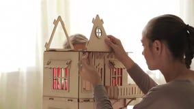 Jong vrouw de bouwpoppenhuis voor haar weinig dochter stock footage