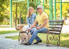 Jong vrouw en blinde met de zitting van de gidshond Royalty-vrije Stock Foto