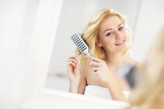 Jong vrouw het borstelen haar Stock Foto's