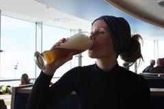 Jong vrouw het drinken bier in restaurant Royalty-vrije Stock Afbeeldingen