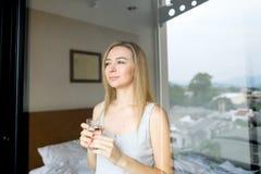 Jong vrouw het drinken glas water bij hotel in ochtend Stock Afbeeldingen