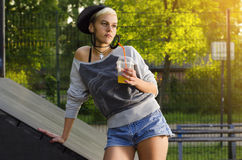 In jong vrouw het drinken sap in vleetpark stock fotografie