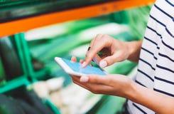 Jong vrouw het winkelen aankoop gezond voedsel op de achtergrond van het supermarktonduidelijke beeld Sluit meningsmeisje opkopen royalty-vrije stock afbeeldingen