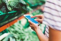 Jong vrouw het winkelen aankoop gezond voedsel op de achtergrond van het supermarktonduidelijke beeld Sluit meningsmeisje opkopen stock foto