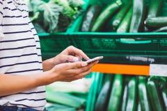 Jong vrouw het winkelen aankoop gezond voedsel op de achtergrond van het supermarktonduidelijke beeld Sluit meningsmeisje opkopen stock afbeelding