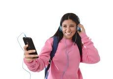 Jong vrouw of studentenmeisje die met mobiele telefoon aan en muziekhoofdtelefoons luisteren die zingen dansen Stock Fotografie