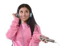 Jong vrouw of studentenmeisje die met mobiele telefoon aan en muziekhoofdtelefoons luisteren die zingen dansen Royalty-vrije Stock Foto's
